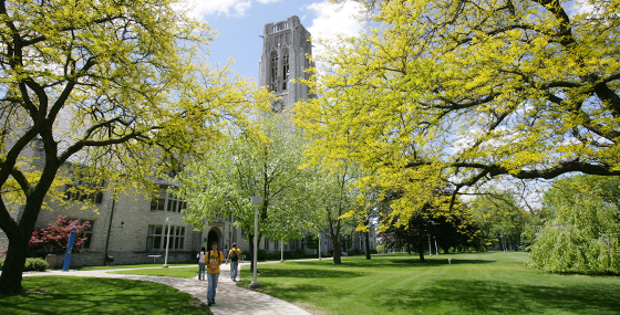 A student walking by University Hall in the spring
