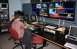 interior shot of UT broadcasting studio with student at the controls