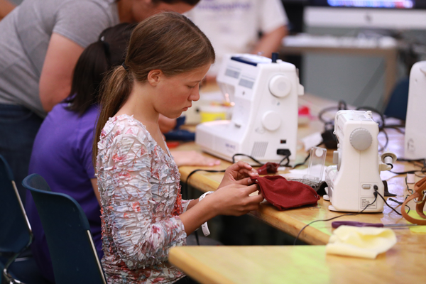 Student using a sewing machine at a UT art workshop