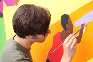 Student Quentin Babcock works on mural at the Frederick Douglass Center