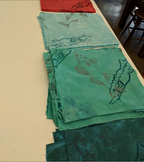 Image of flags with fish drawings on them, in preparation for the Dialogue with the River interactive art project