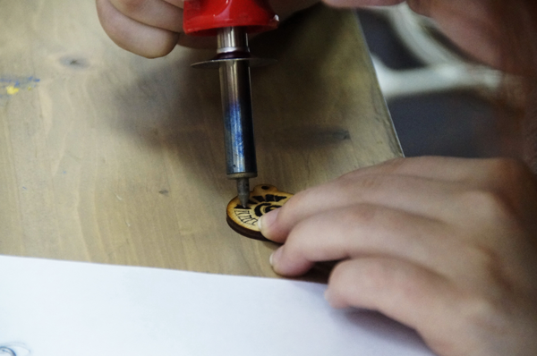 Student using a woodburning tool