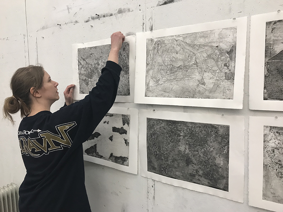 student pinning artwork to wall