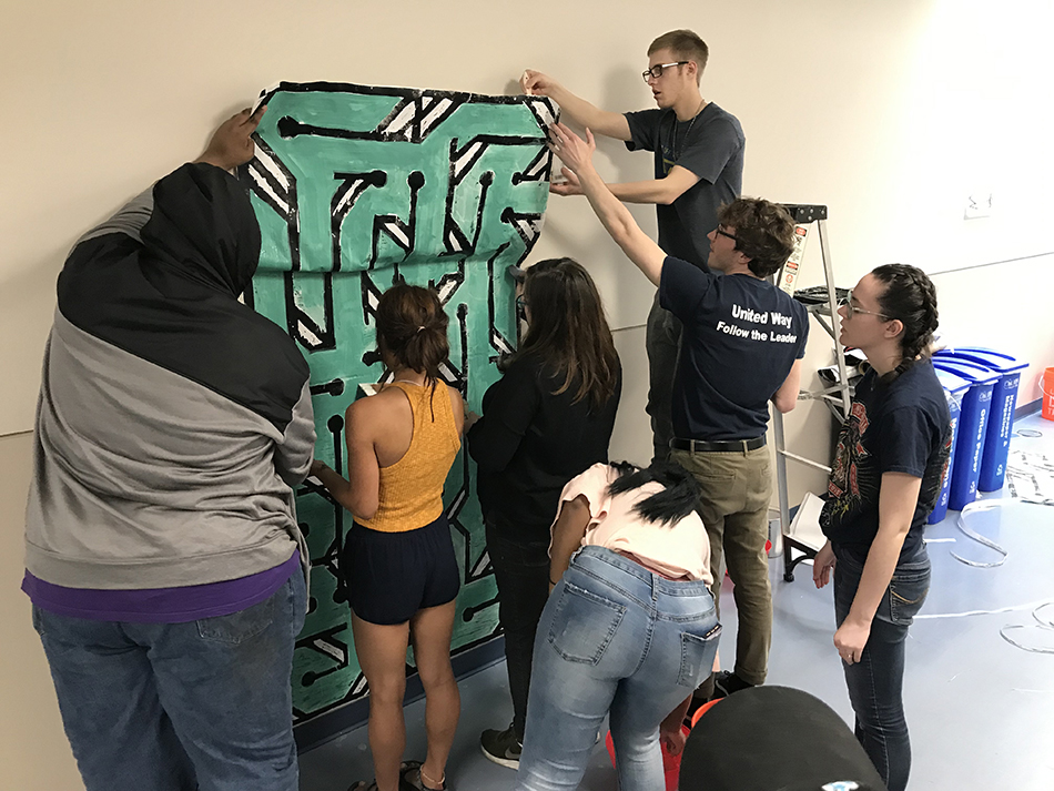 Students attaching a paper mural in the UT Incubator Research unit.