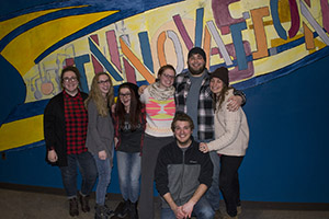 students standing in front of their wheat pasted mural
