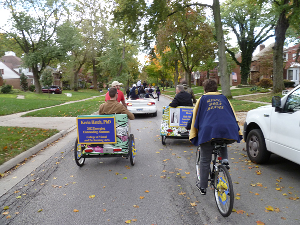 Riding through the streets on the parade route, Kevin Hatch and Dick Putney in pedicabs and Associate Dean, Monsos wearing a cape and pedaling her way through the parade route.