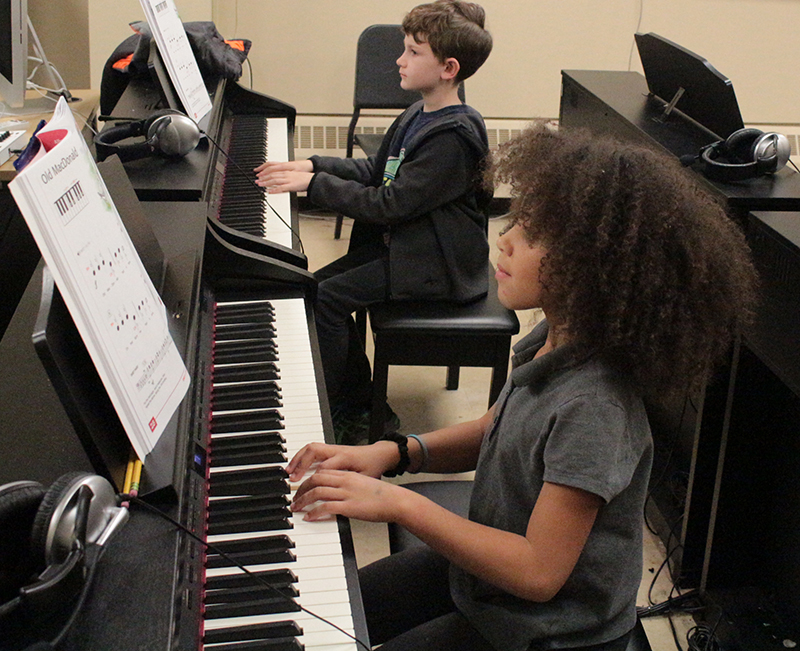 Child at a piano in a piano class presented by the UToledo Department of Music
