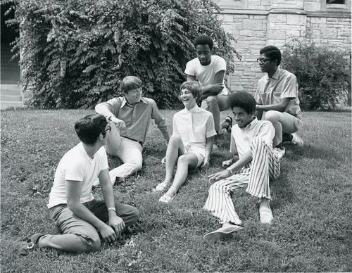 A group of students from the 60s chatting outside.