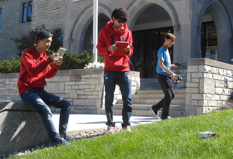 Three students navigating the grass
