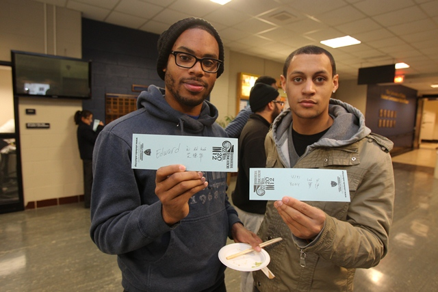 two students showing their names written in Arabic