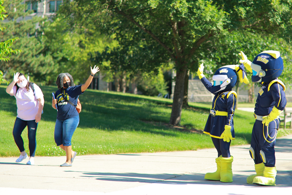 Rocky and Rocksy waving to students on a sunny day