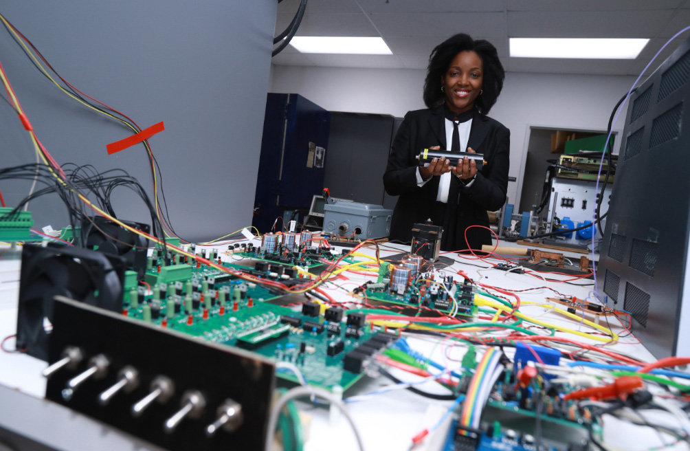 Dr. Ngalula Mubenga with various electronics