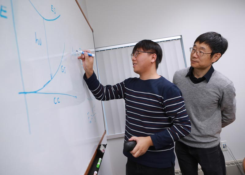 Dr. Yan working with a student on a formula