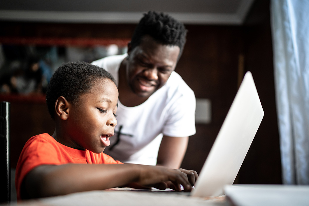 A father watching his son engage in remote learning on a laptop
