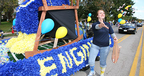 Girl throwing candy from a float at the homecoming parade