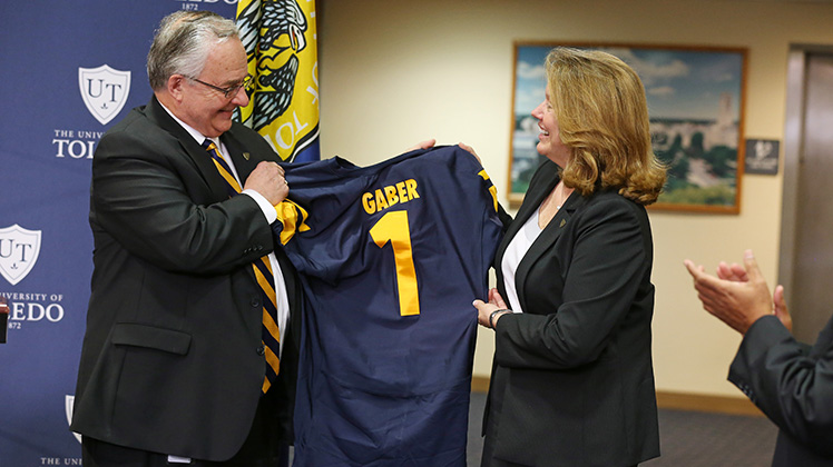 Dr. Gaber holding up a UT football jersey
