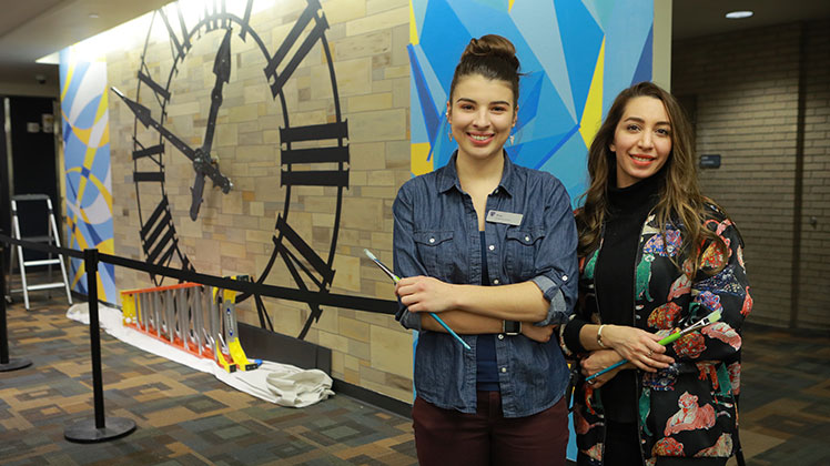 Rose Mansel-Pleydell and Tara Yarzand with clock mural in Carlson Library.