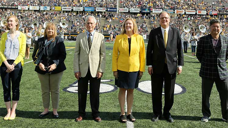 Photo of outstanding alumni receiving awards on football field.