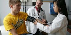 PA students taking blood pressure of patient