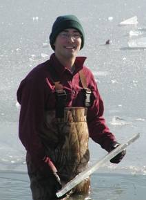 Ecology student collects aquatic samples through the ice at Lake Erie Center