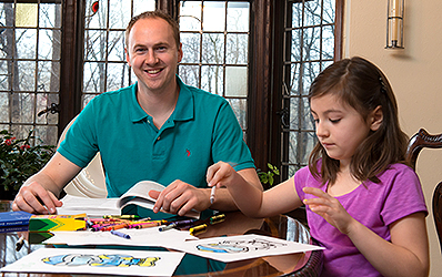 UT student at home doing his homework with daughter coloring