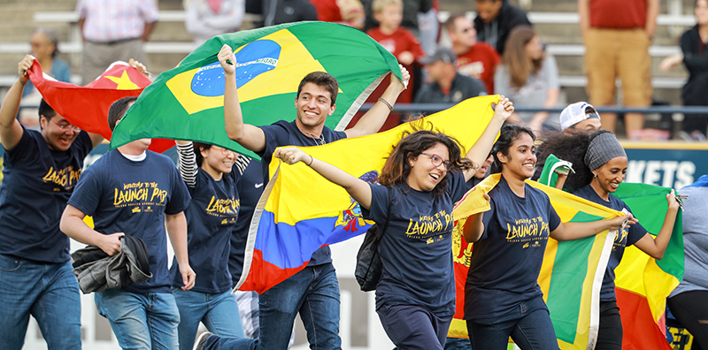 International students running with flags on football field