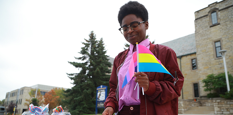 Student holding bisexual and pansexual flags