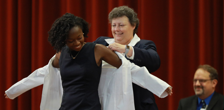 A student receiving her white coat