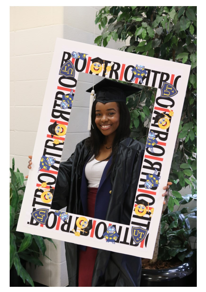 Graduate holding TRIO sign