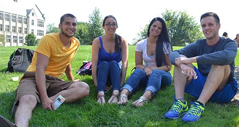 group of students sitting in grass on campus